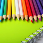 Bright multicolor pencils on green notebook